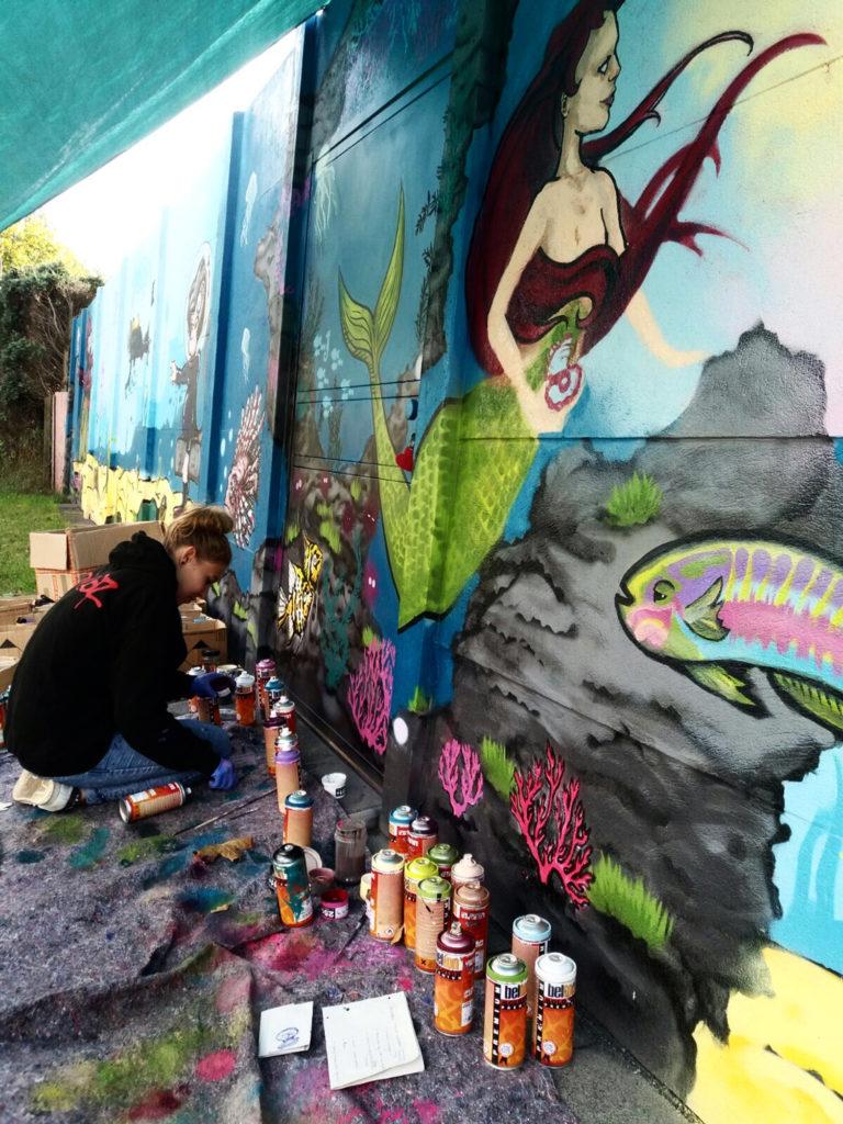 Laura kniet vor der bunten Mauer und malt sie an