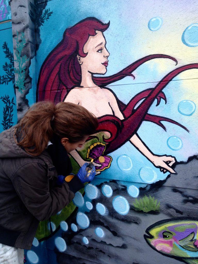 Verena zeichnet akkurat mit Lack die Perle in der Muschel