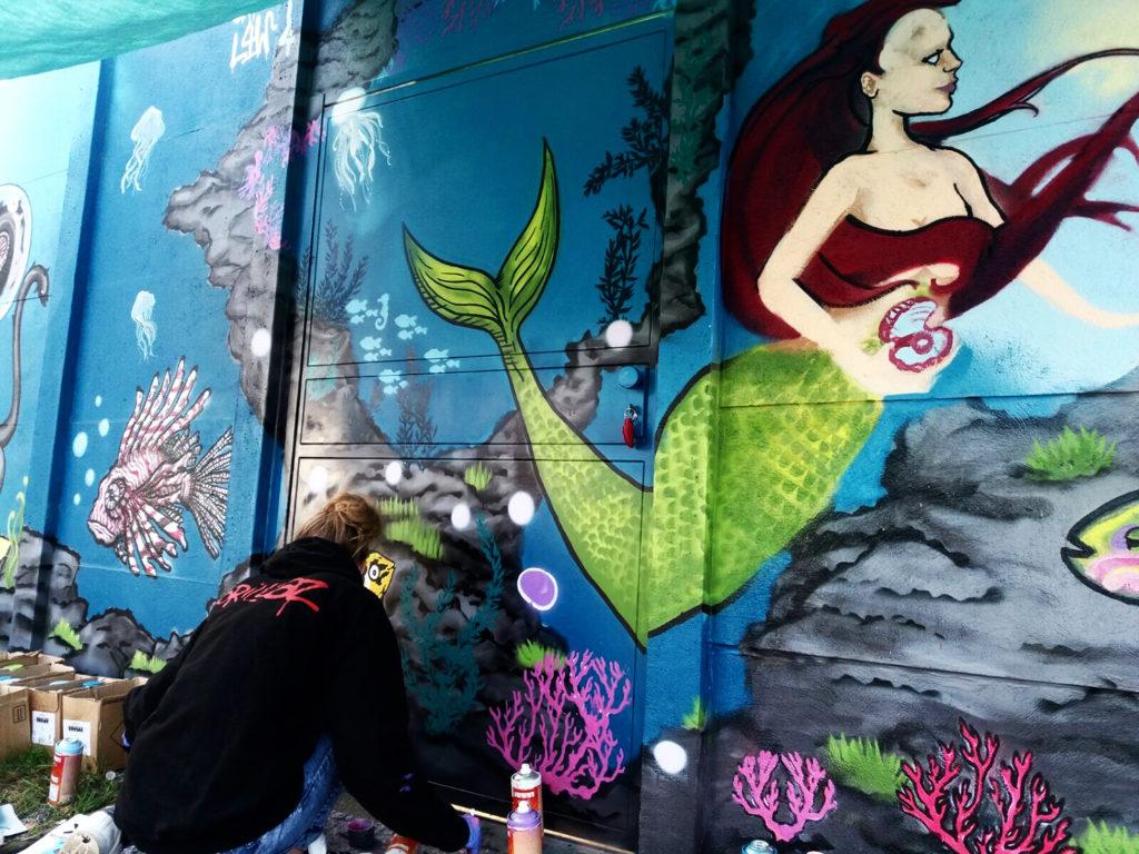 Laura vor der bunten Unterwasserwelt